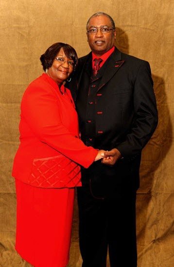 Deacon Tommy and Sue Haliburton standing together in color cordinated red and black suit and dress.